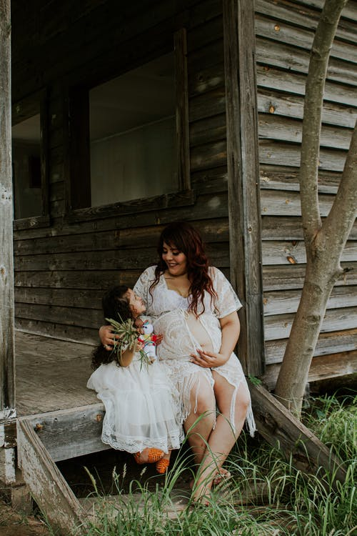 Positive expectant woman with little daughter on wooden terrace
