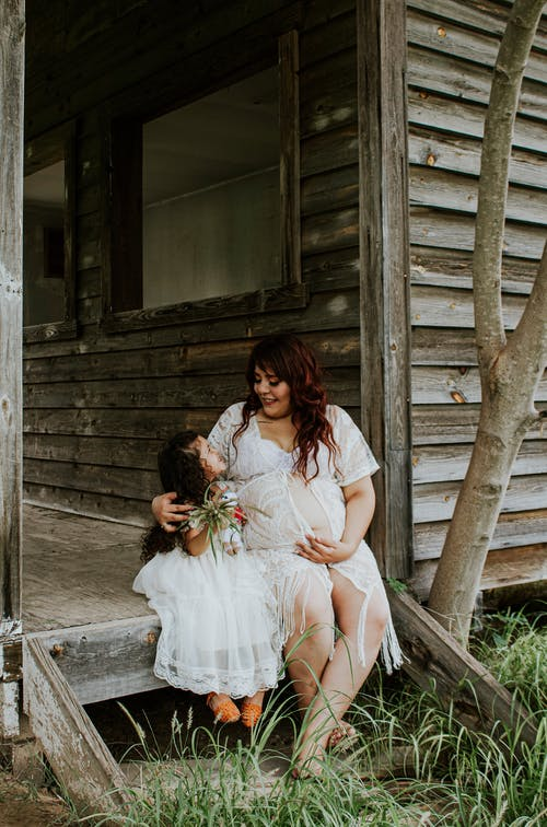 Content expectant woman embracing trendy girl on old porch
