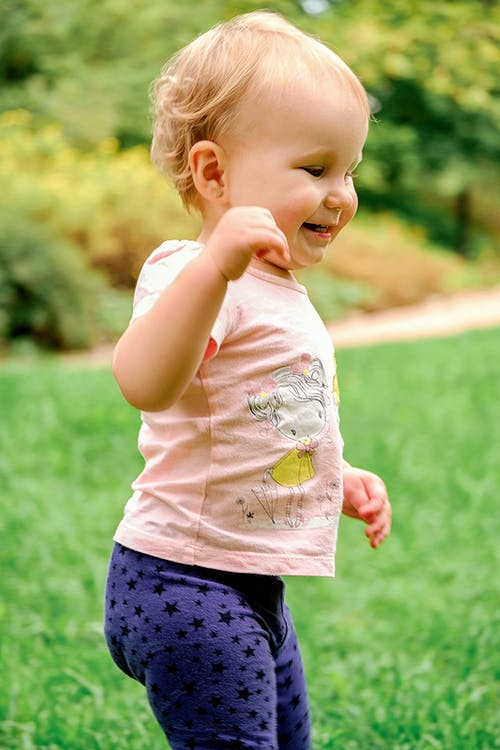 Side view of content toddler child in casual wear standing with raised arm on colorful green lawn while looking away