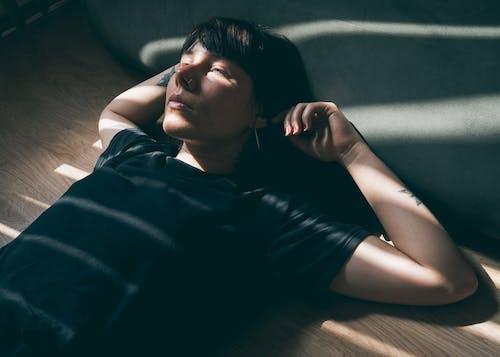 Woman in Black Crew Neck T-shirt Lying on Brown Sofa