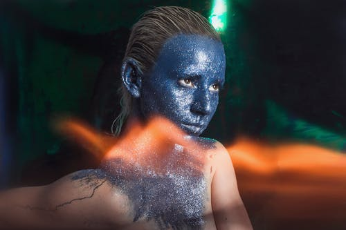 Thoughtful woman with blue paint on face