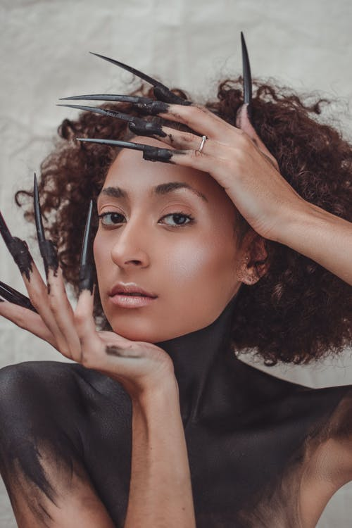 Ethnic female model with body art and long false nails
