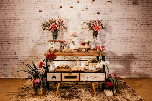 Wooden cabinet decorated with flowers bouquets and desserts