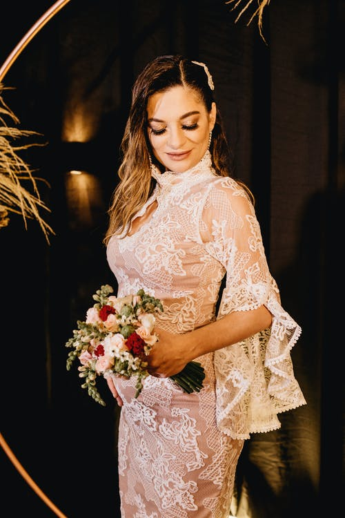Serene pregnant bride wearing classic lace white dress with fragrant bouquet standing in dark studio while touching belly gently and looking down with smile