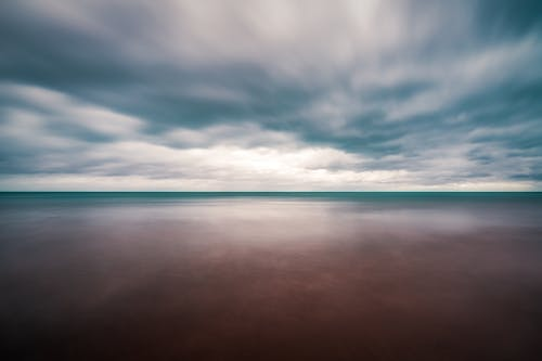 Long exposure wonderful view of peaceful endless sea with turquoise water beneath dramatic cloudy sky