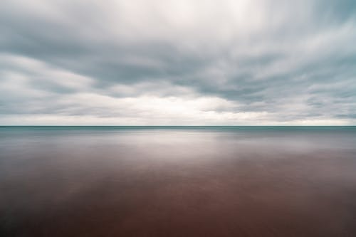 Long exposure scenery of dramatic cloudy sky over tranquil blue sea on overcast weather
