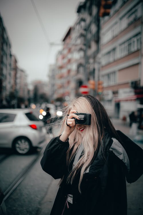 Cheerful female taking photos on busy street