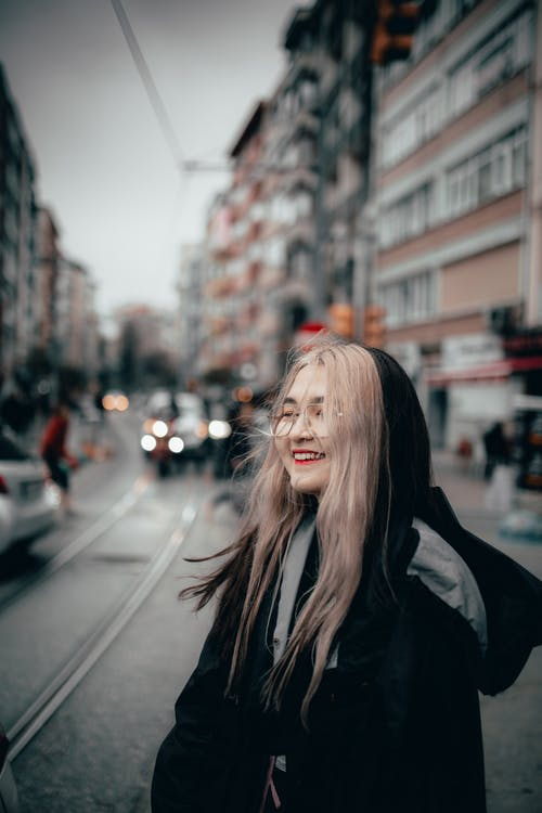 Delighted Asian female in black warm hoodie standing on busy city street with sincere smile