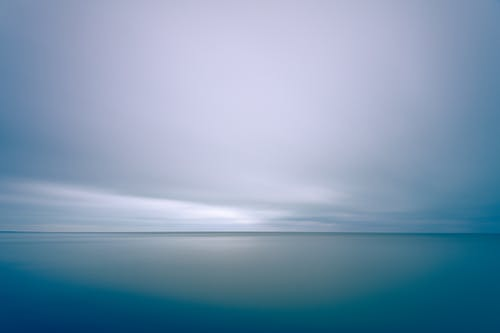 Long exposure scenic shot of endless tranquil sea with clean turquoise water beneath majestic cloudy sky
