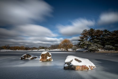 Snowy stones on frozen lake surface in winter countryside