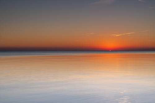 Magnificent scenery of tranquil sea beneath picturesque sunset sky and reflecting bright red sunlight