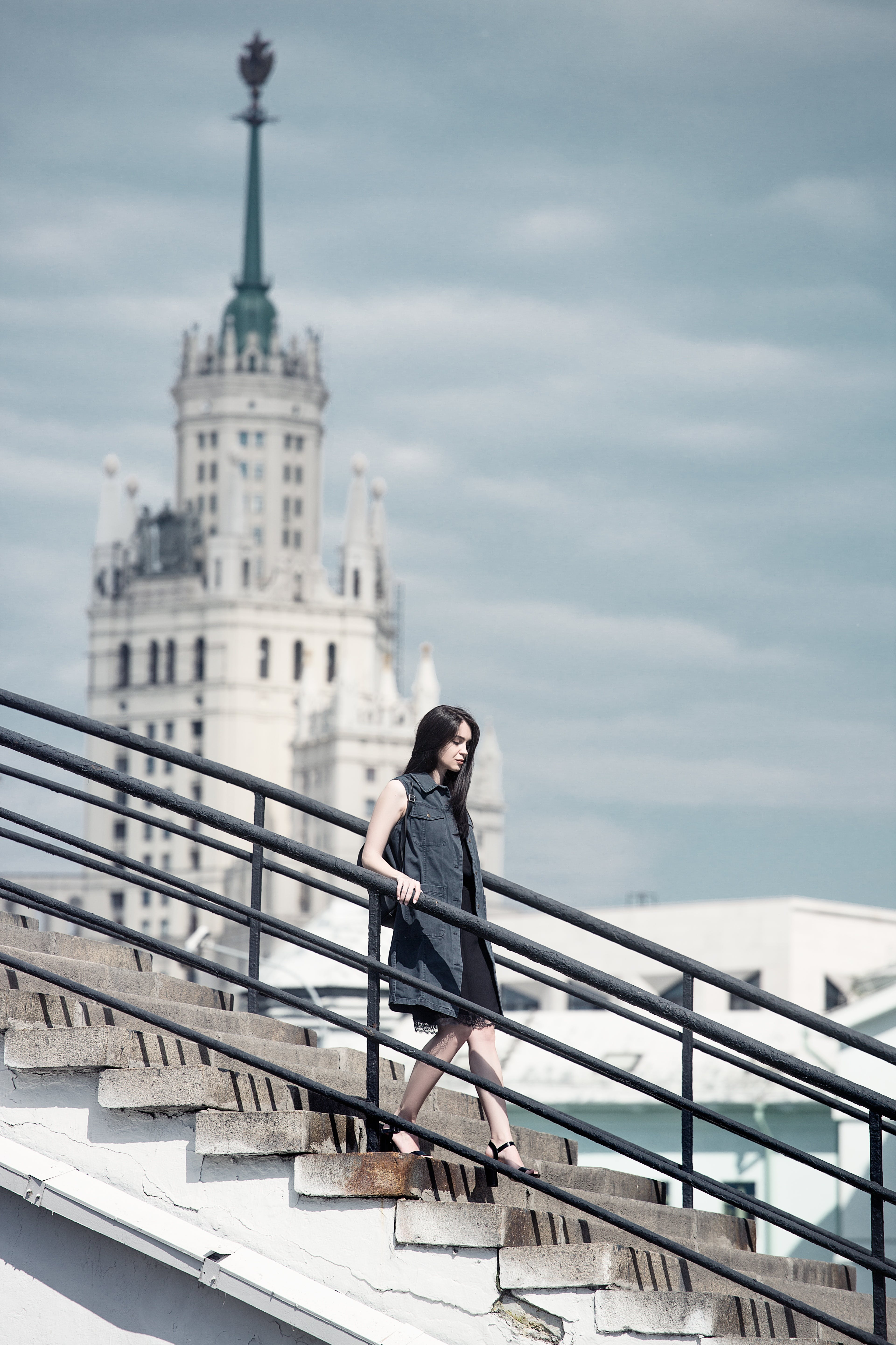Woman Walking on Gray Concrete Stair Under Gray Sky