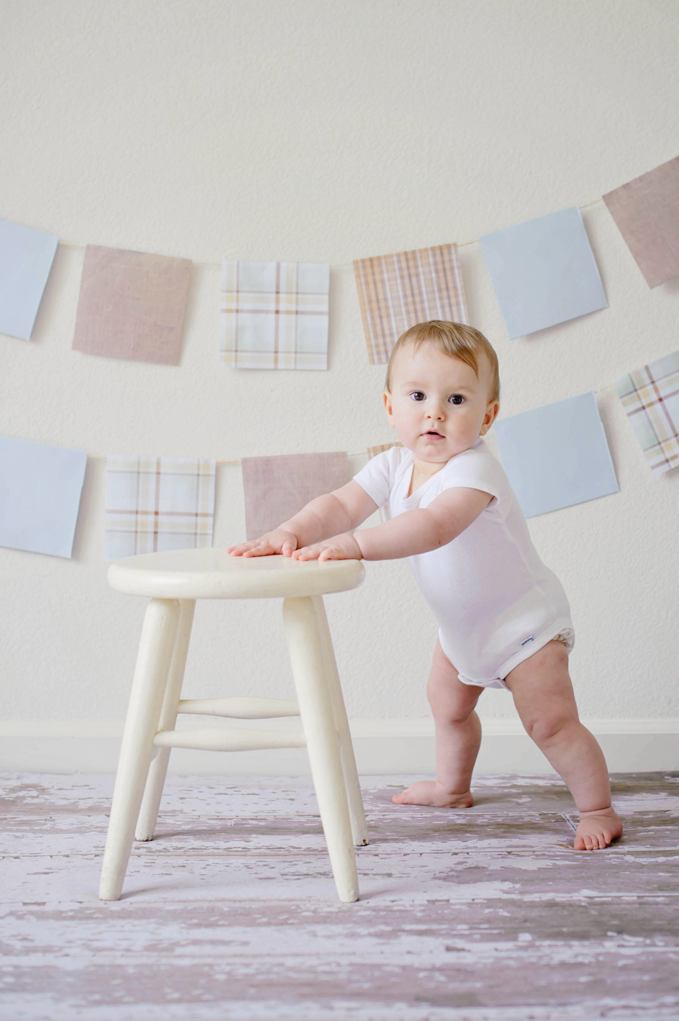 Baby Holding White Wooden Stool
