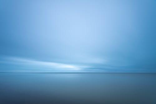Blue seascape under cloudy evening sky