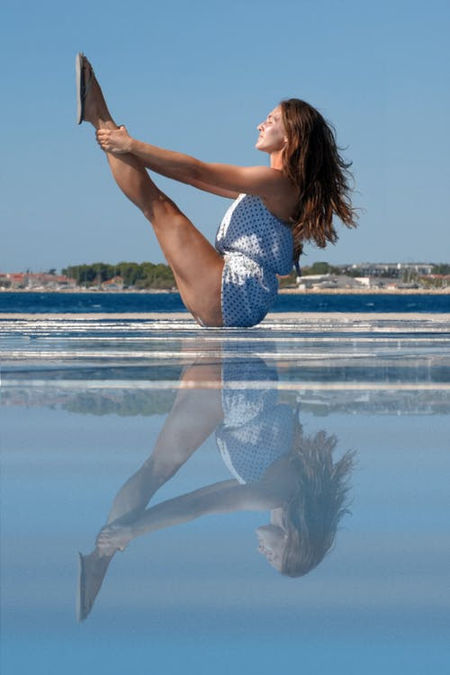 Side view of concentrated young fit female traveler with long hair performing Urdhva Mukha Pascimottanasana pose during yoga session on seashore against blue sky