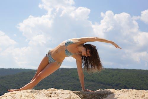 Fit woman in swimwear doing Side Plank on rocky hill
