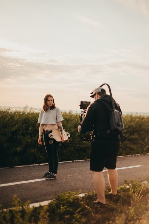 Unrecognizable photographer shooting woman with longboard in countryside