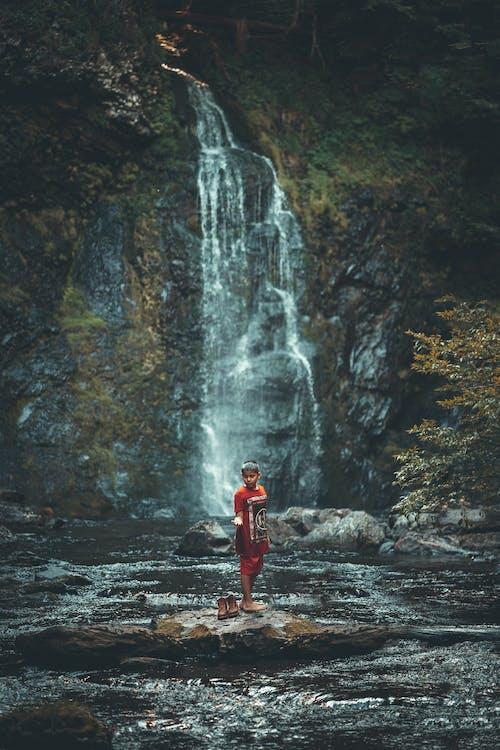 Man in Red Jacket Standing on Rock Near Waterfalls