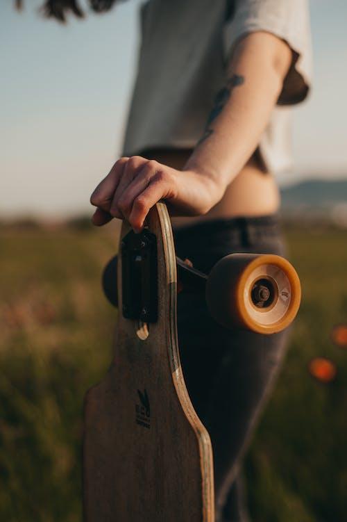 Faceless woman near wooden longboard