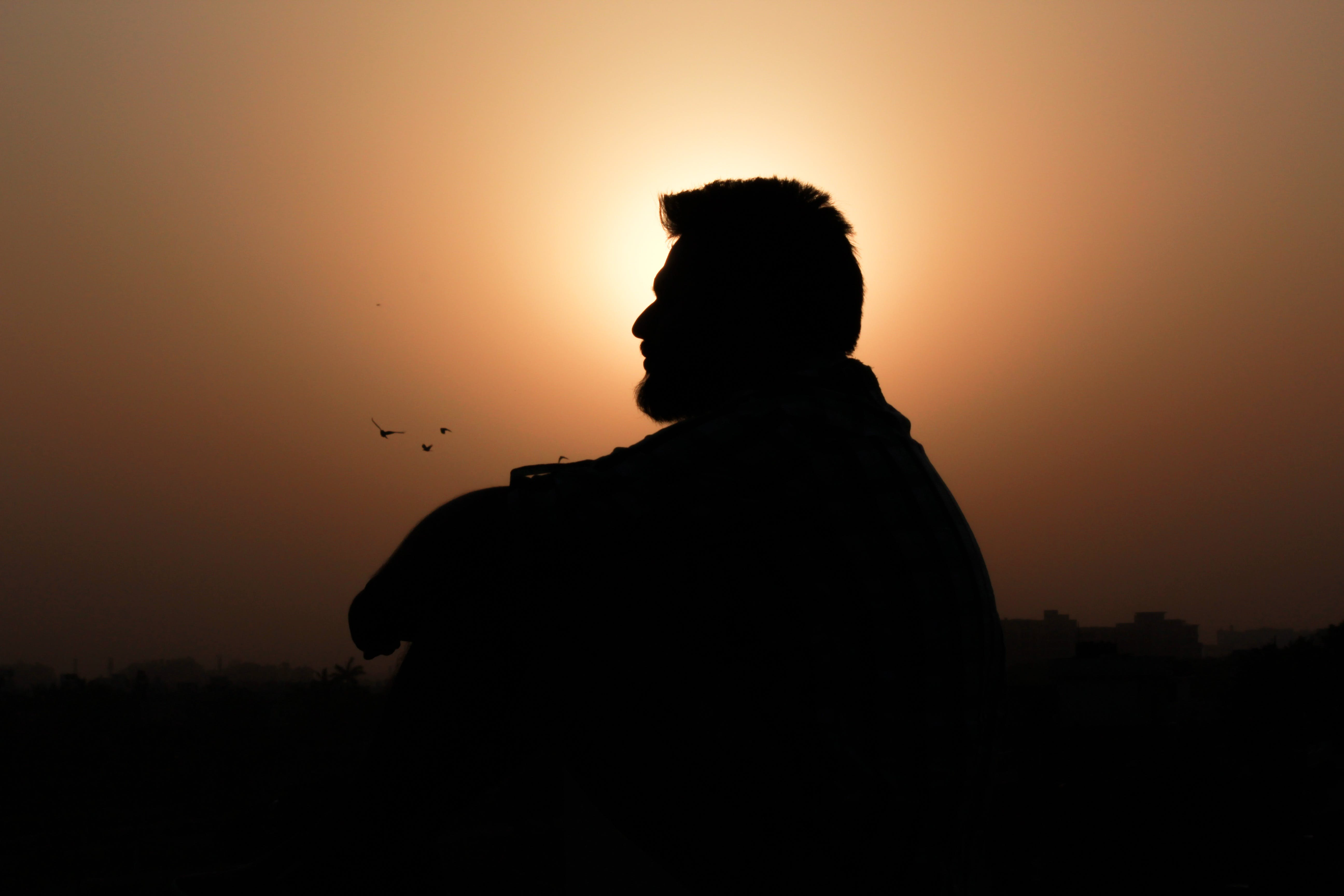Silhouette of Sunset Sitting Man