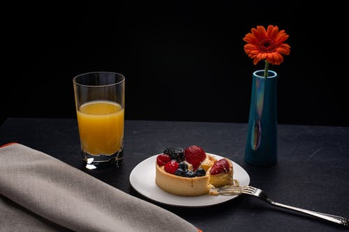 High angle of plate with delicious cheesecake decorated with berries placed on table with orange juice and vase with red gerbera
