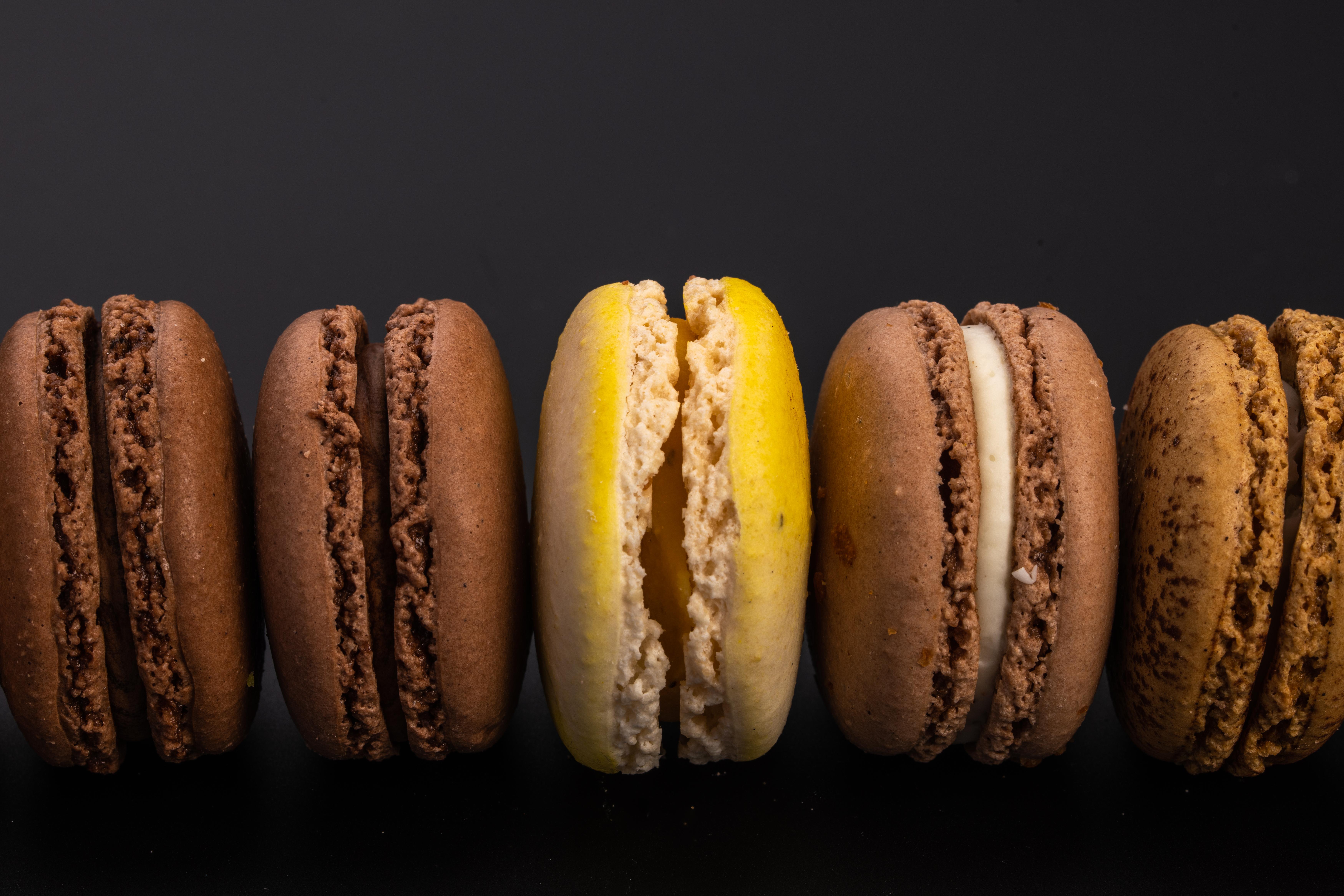 set of various macaroons on black background