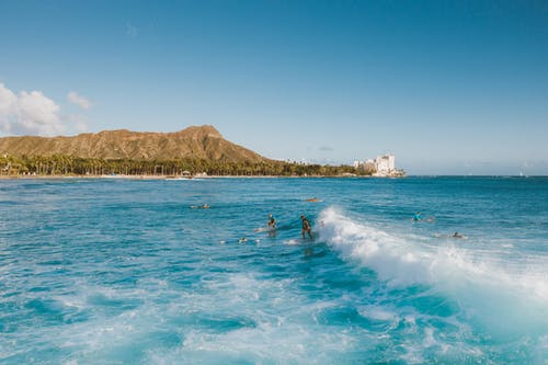 People Surfing on Sea Near Mountain Under Blue Sky