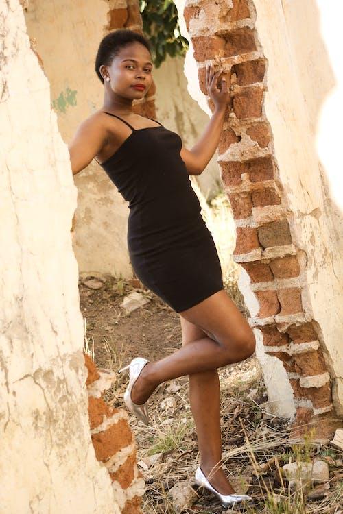 Young black in elegant dress in destroyed building