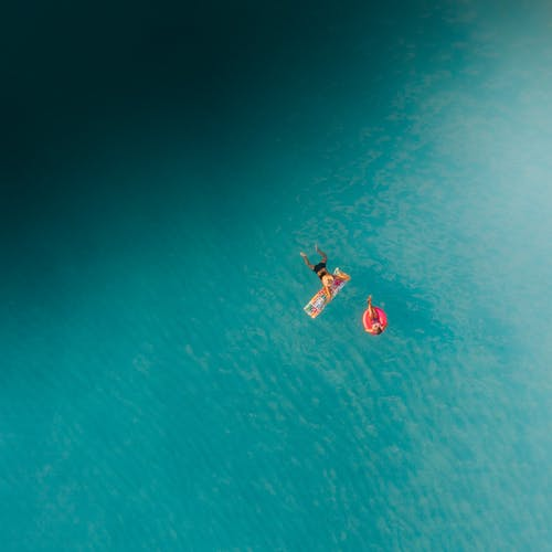 2 Person in Red and White Wetsuit Surfing on Blue Water