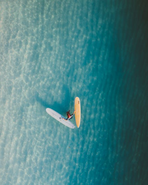 Aerial View of Person Riding on White Boat on Blue Sea