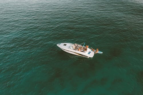 White and Brown Boat on Green Water