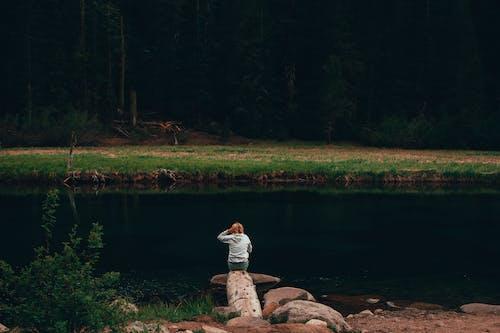 Woman in White Long Sleeve Shirt Sitting on Rock Near Lake