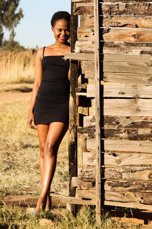 Stylish woman standing near wooden wall