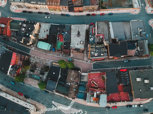 Aerial view of roofs of aged dwelling buildings near asphalt roadways with driving cars in town