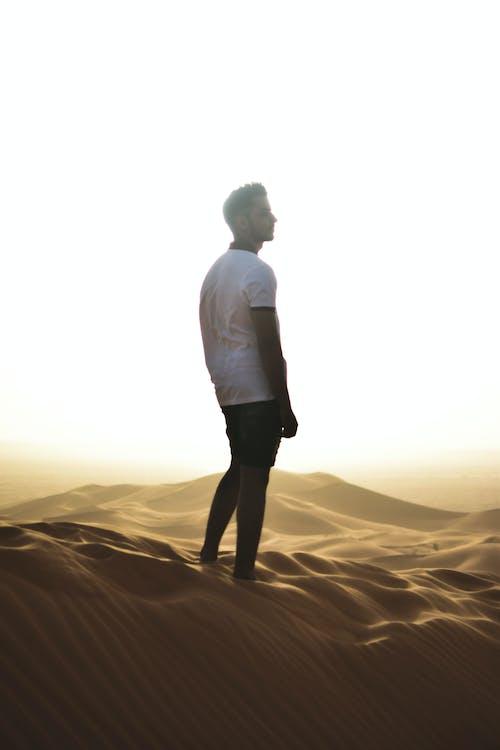 Man in White Dress Shirt Standing on Sand