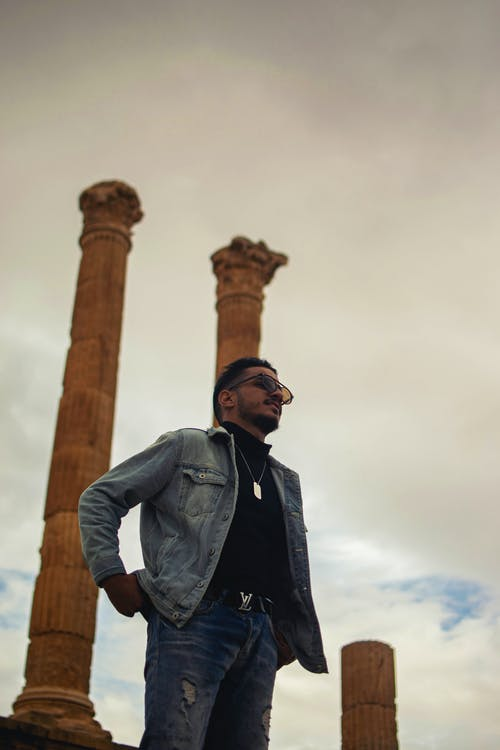 Man in Black Leather Jacket Standing Near Brown Concrete Post