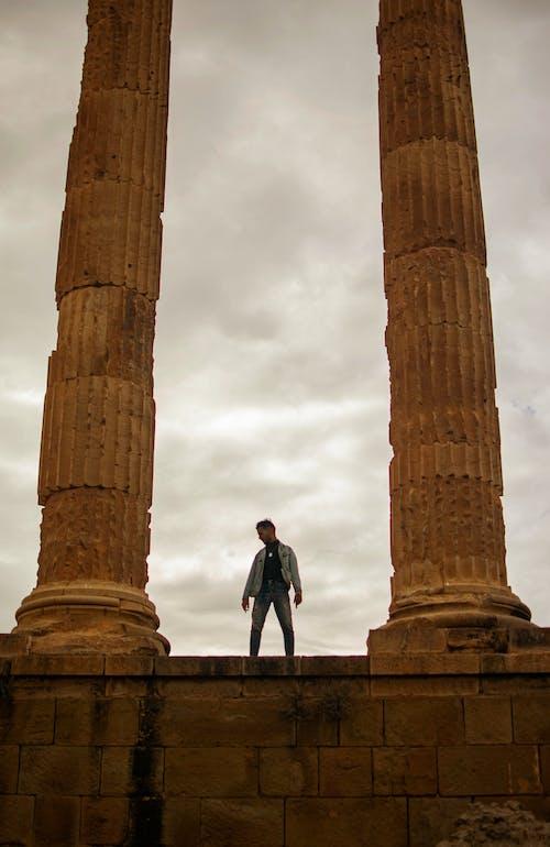 Man in Black Jacket and Blue Denim Jeans Standing Near Brown Concrete Pillar
