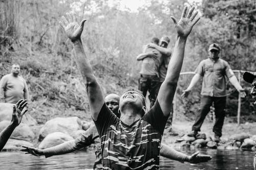 Grayscale Photo of Man in Stripe Shirt Raising His Hands