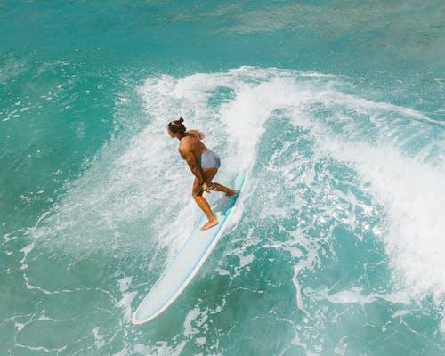 Woman in Black Bikini Holding White Surfboard on Body of Water