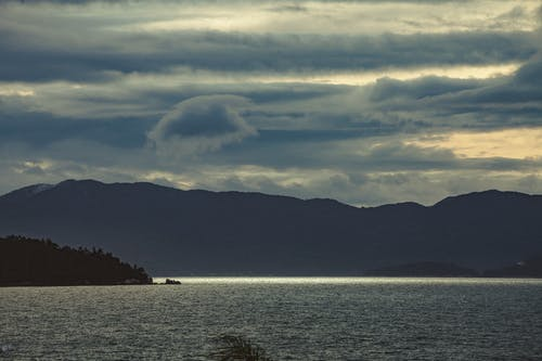 Picturesque view of rippled ocean near mountains under sky with clouds at sundown