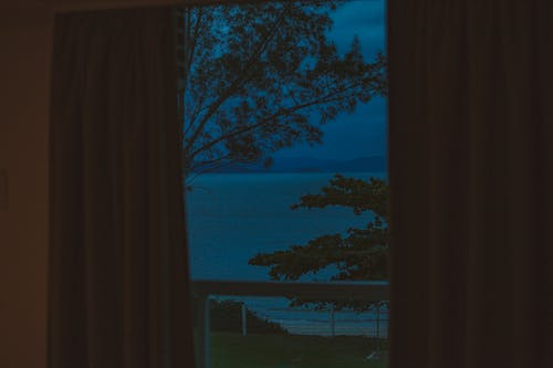 From fenced balcony view of silent ocean near trees behind mount silhouettes under sky at dusk