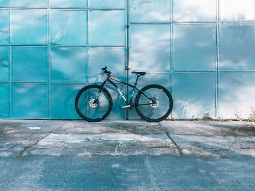 Contemporary bike parked on shabby concrete pavement near glowing metallic wall in daylight