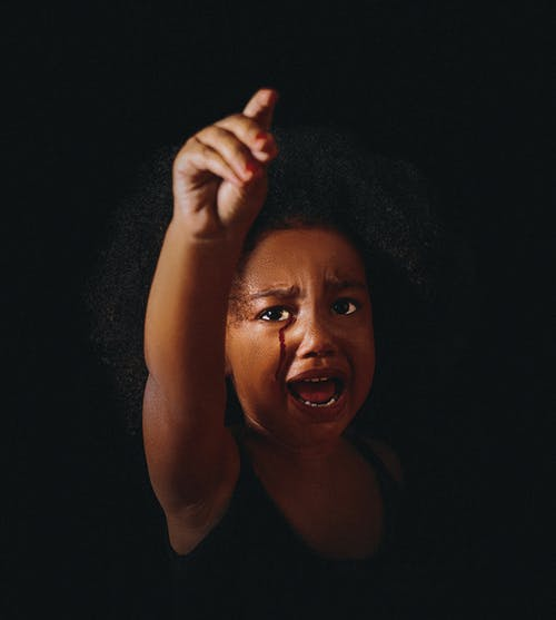 Black child with raised arm crying on black background