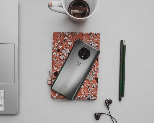 Top view of contemporary cellphone on diary near earphones and pencils with cup of coffee