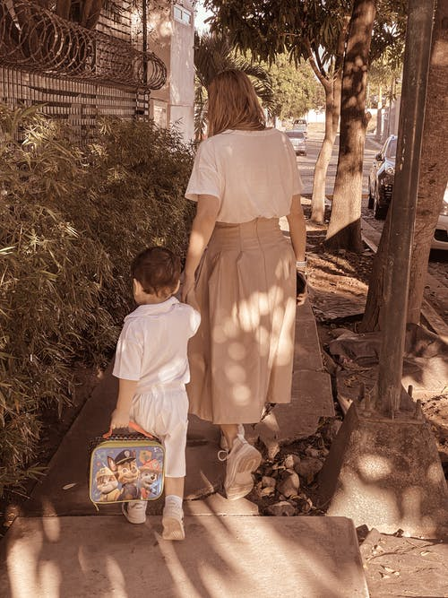 Unrecognizable mother holding by hand son while walking on street