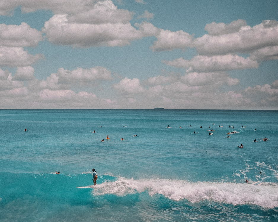 People Surfing on Sea Waves Under White Clouds and Blue Sky