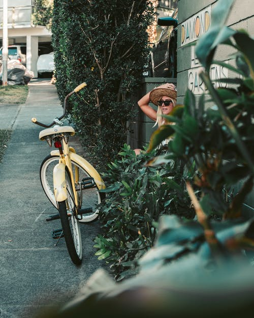 Person Riding on Bicycle Near Green Plants