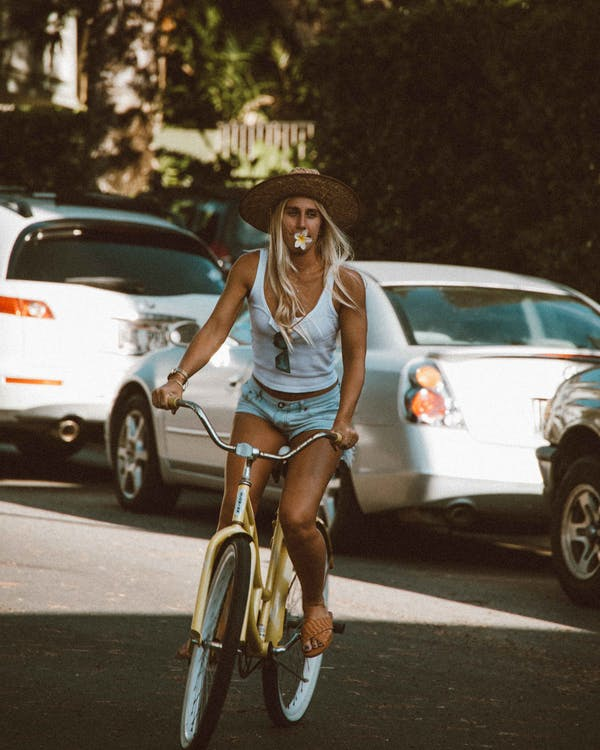 Woman in Blue Tank Top and Blue Denim Shorts Riding on Bicycle