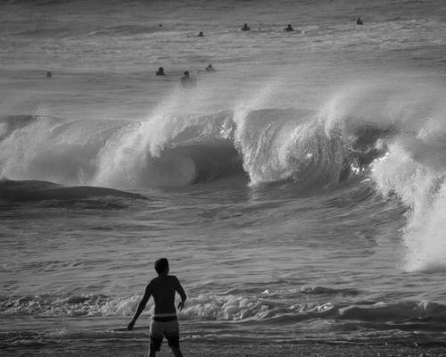Man in Black Shirt and Pants Walking on Beach Shore