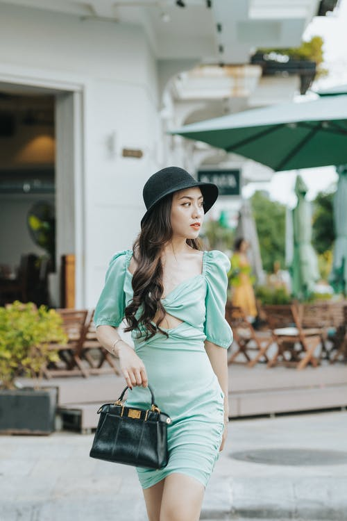 Young wistful ethnic female in elegant apparel with leather handbag in hat looking away while walking on pavement